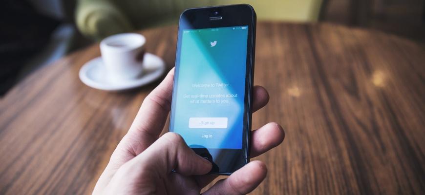 Hand mit iPhone und Twitteraccount